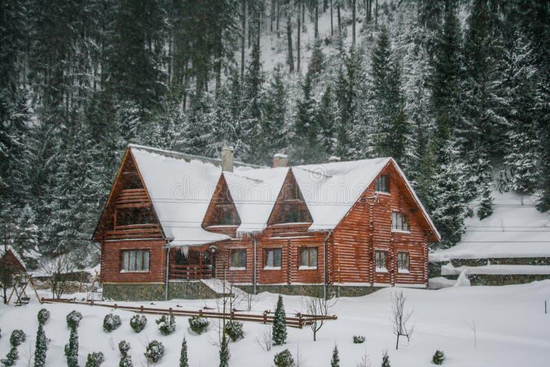 Casa de madera nevosa del viejo vintage Invierno Montañas y bosque fotos de archivo libres de regalías