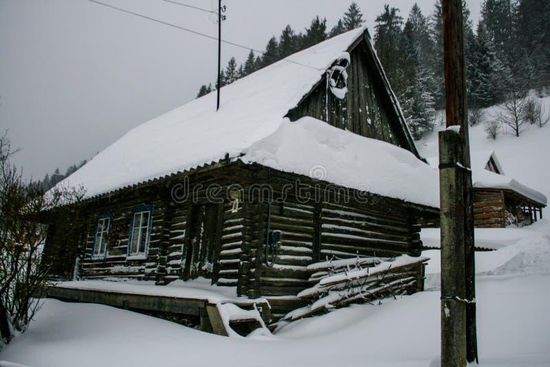 Casa de madera nevosa del viejo vintage Invierno Montañas y bosque fotografía de archivo