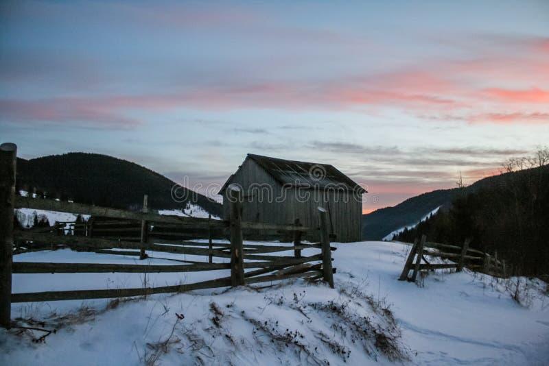 Casa de madera nevosa del viejo vintage Sol del invierno Montañas y bosque fotos de archivo