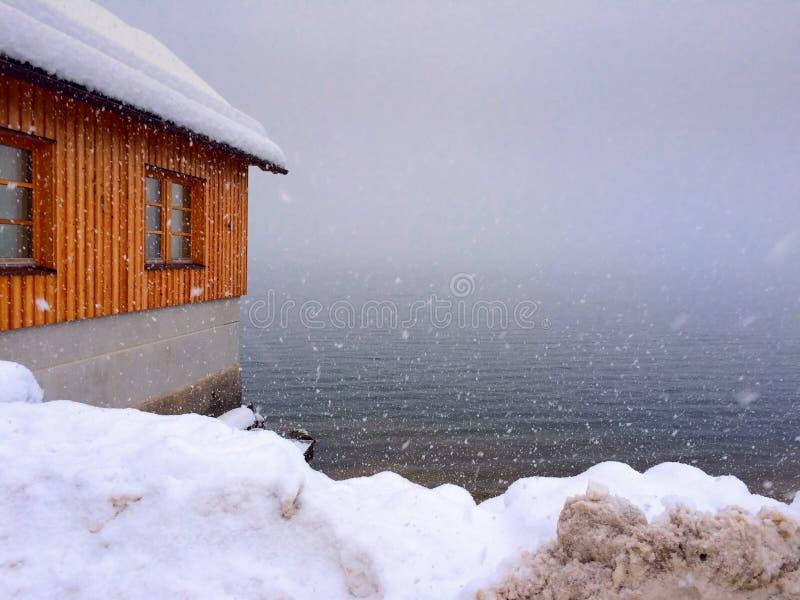 Casa de madera por el lago, nevando fotos de archivo