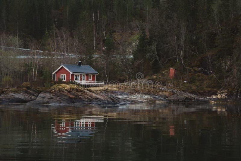 Casa de madera roja cerca del lago contra la perspectiva del bosque y de las montañas Reflexi?n en agua imagen de archivo libre de regalías