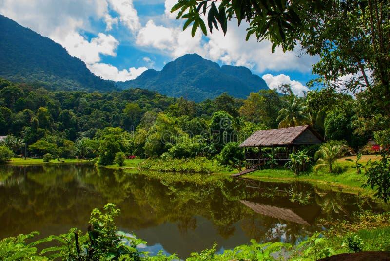Casa de madera tradicional cerca del lago y montaña en el fondo Kuching al pueblo de la cultura de Sarawak Borneo, Malasia imagenes de archivo