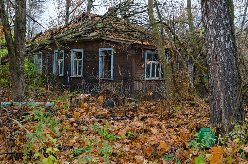 Casa de madera de un piso abandonada en la parte no residencial de Chernóbil, zona de exclusión de NPP de Chernóbil, Ucrania imagen de archivo