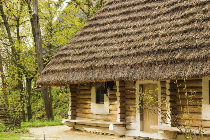 Casa de madera vieja con el tejado cubierto con paja en pueblo foto de archivo