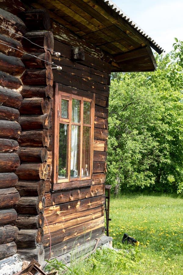 Casa de madera vieja con la ventana cerca de árboles verdes en concepto que cultiva un huerto del verano fotos de archivo