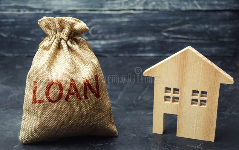 Casa de madera y un bolso con el préstamo de la palabra Compra de un hogar en deuda Inversión de la familia en concepto de las pr imagen de archivo