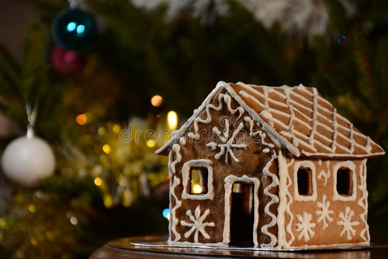 Casa de pão-de-espécie caseiro do Natal Luzes e bolas bonitas da árvore no fundo fotografia de stock royalty free