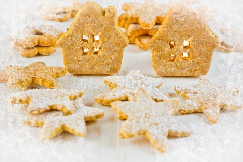Casa de pão-de-espécie do Natal, estrelas e cookies do linzer no fundo de madeira branco, luz da vela, vinheta floral da textura  fotografia de stock