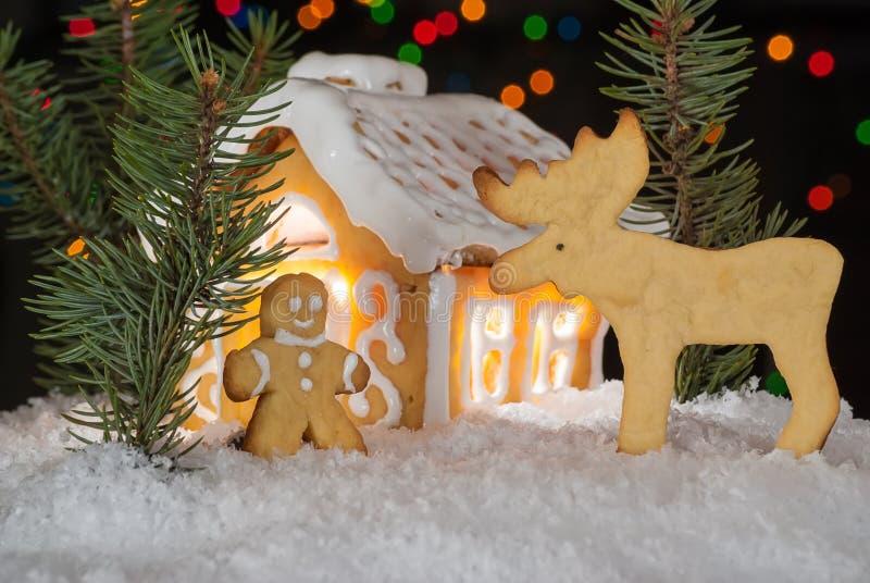 Casa de pan de jengibre con el hombre de pan de jengibre, los alces y los árboles de navidad fotografía de archivo libre de regalías