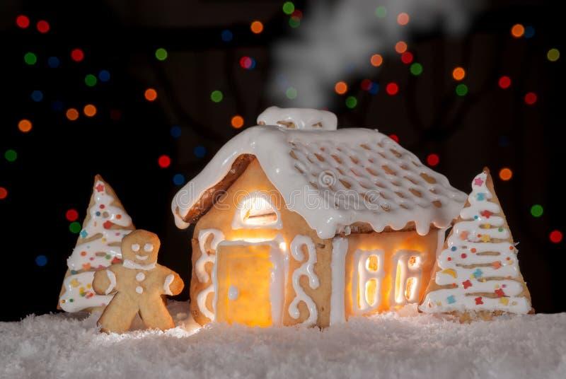 Casa de pan de jengibre con el hombre de pan de jengibre y los árboles de navidad foto de archivo