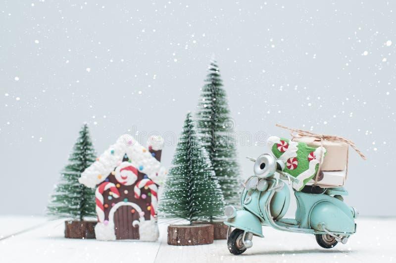 Casa de pan de jengibre del juguete en ingenio de la ciudad y de la moto de los árboles de navidad foto de archivo libre de regalías