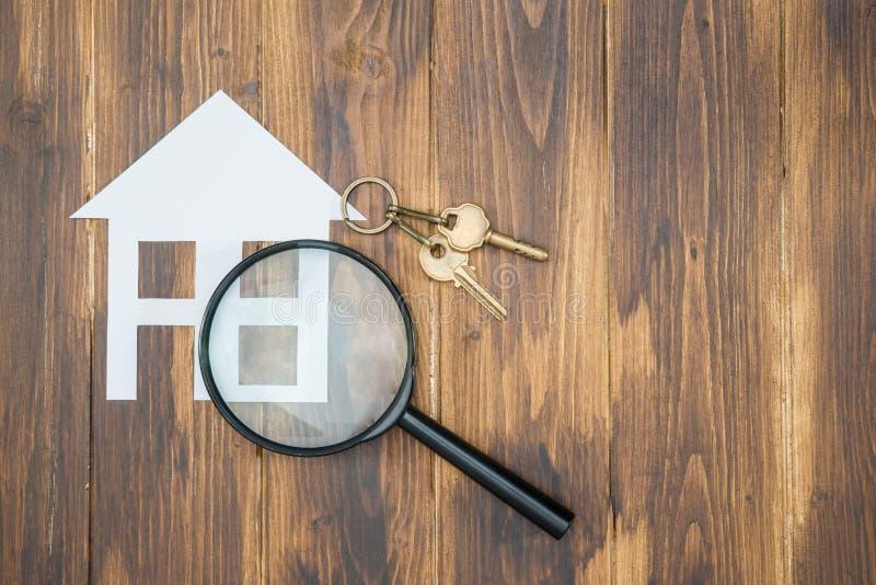 Casa de papel e chave com lupa, procura de casa fotos de stock royalty free