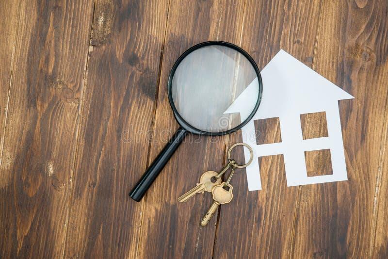 Casa de papel e chave com lupa, procura de casa fotografia de stock