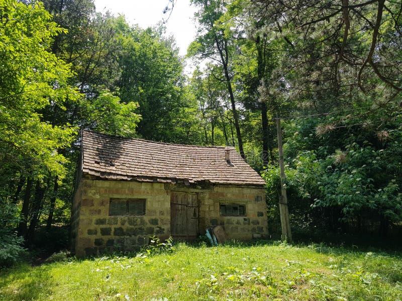 Casa de pedra abandonada pequena no meio de uma floresta verde fotos de stock royalty free