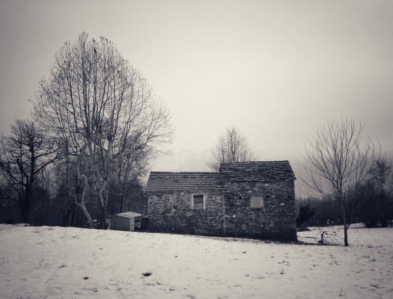 Casa de pedra com neve nos cumes italianos fotos de stock royalty free