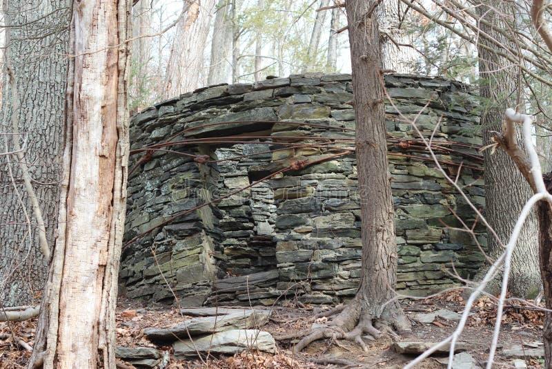 Casa de pedra velha nas madeiras imagens de stock royalty free