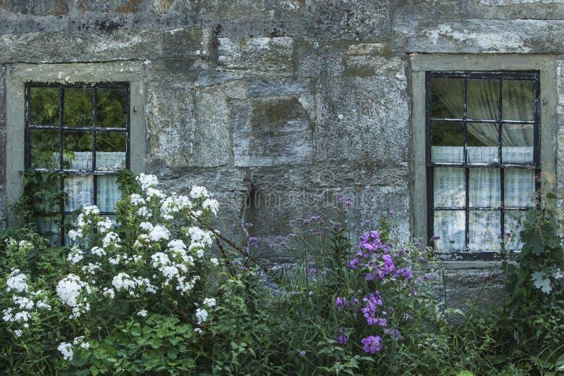 Casa de piedra antigua con Windows imagen de archivo libre de regalías