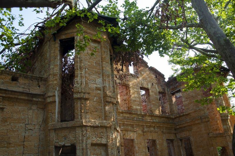 Casa de piedra destruida amarilla antigua vieja en la yarda con los árboles alrededor Pobreza y miseria, del sur, verano foto de archivo