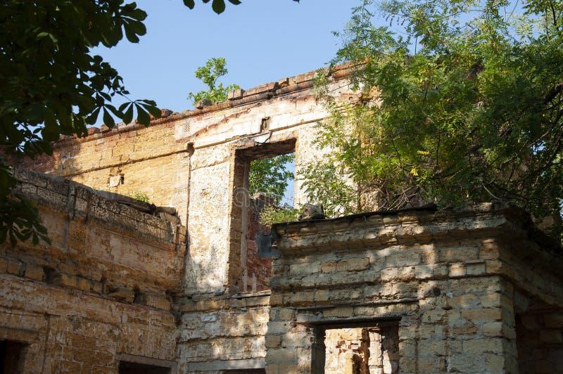 Casa de piedra destruida amarilla antigua vieja en la yarda con los árboles alrededor Pobreza y miseria, del sur, verano imagen de archivo libre de regalías