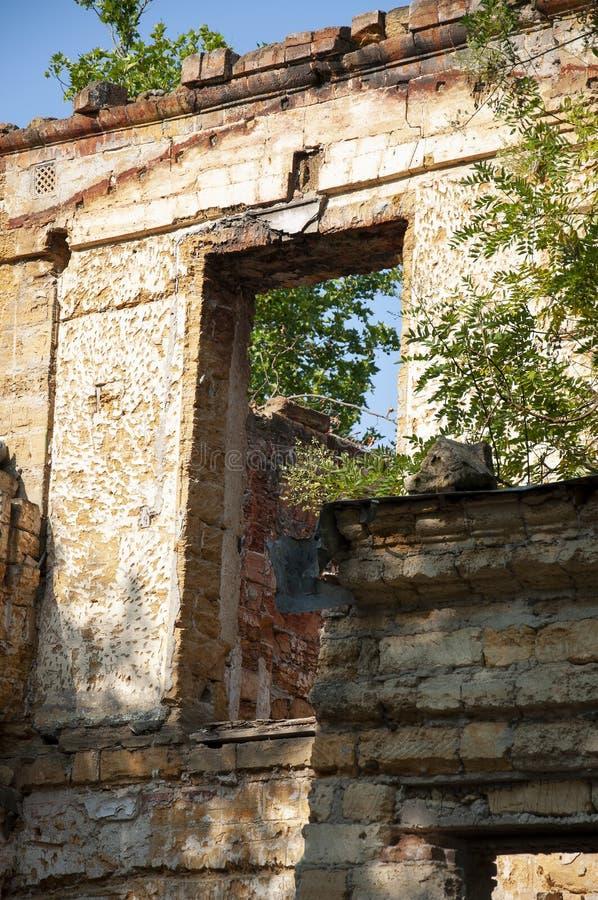 Casa de piedra destruida amarilla antigua vieja en la yarda con los árboles alrededor Pobreza y miseria, del sur, verano imagenes de archivo