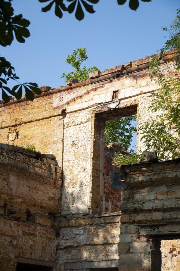 Casa de piedra destruida amarilla antigua vieja en la yarda con los árboles alrededor Pobreza y miseria, del sur, verano fotos de archivo libres de regalías