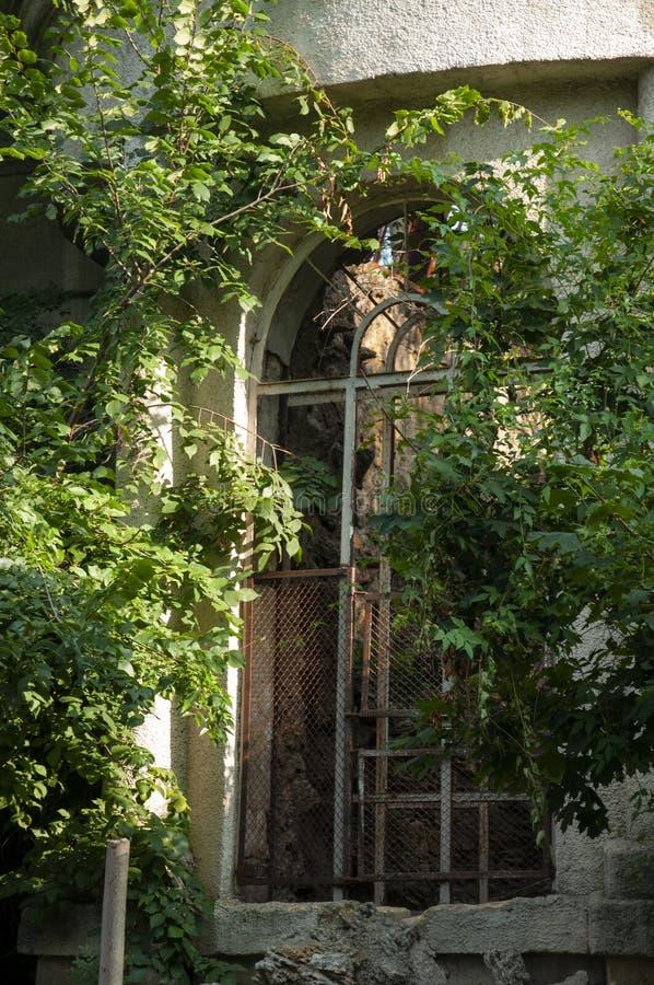 Casa de piedra destruida blanca antigua vieja en la yarda verde con los árboles alrededor Pobreza y miseria, del sur, verano foto de archivo