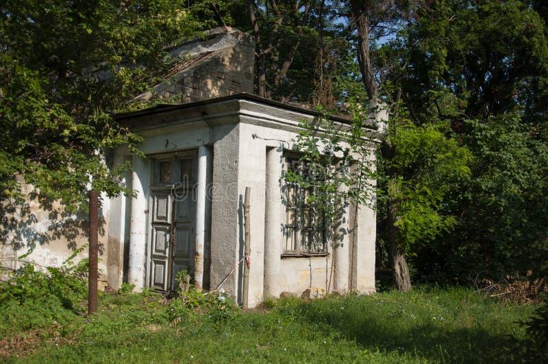 Casa de piedra destruida blanca antigua vieja en la yarda verde con los árboles alrededor Pobreza y miseria, del sur, verano imagen de archivo