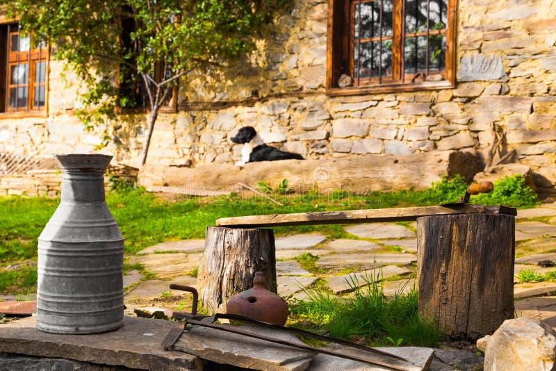 Casa de piedra rústica con la jarra vieja del metal, Leshten, Bulgaria foto de archivo libre de regalías