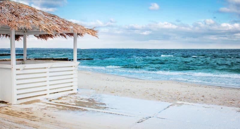 Casa de planta baja en una playa arenosa por el mar foto de archivo
