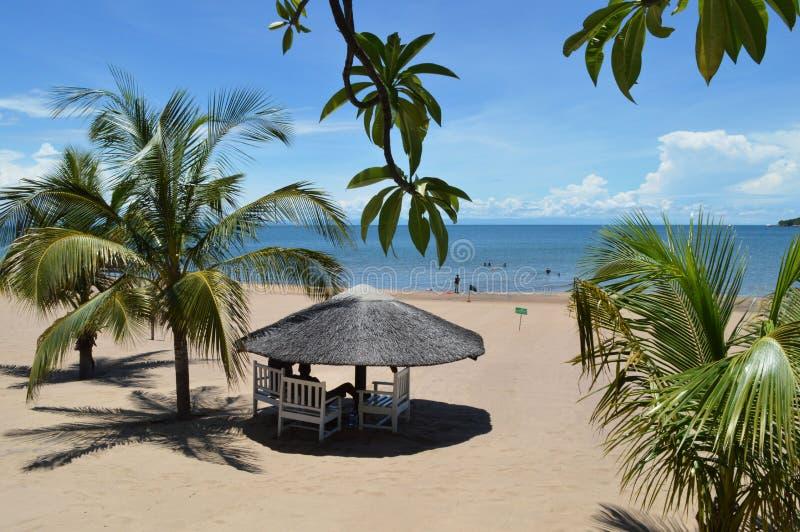 Casa de planta baja de madera blanca rodeada por las hojas de palma en la playa de sorprender el lago Malawi o Nyasa en África imágenes de archivo libres de regalías