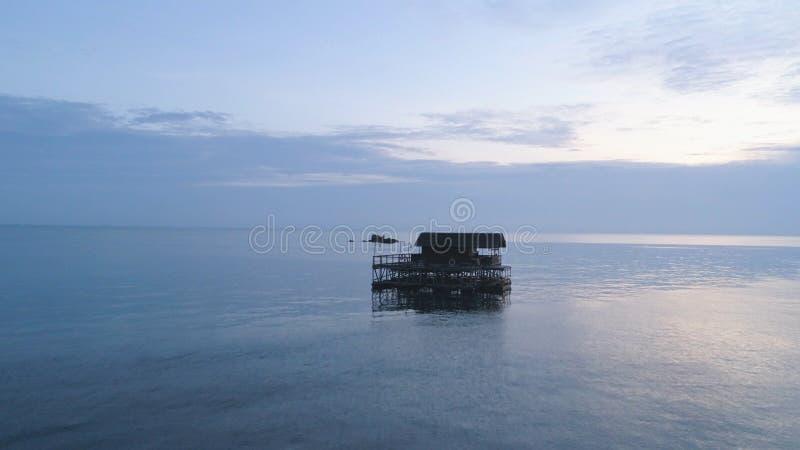 Casa de planta baja de madera hermosa rodeada por el agua impresionante del océano tiro Aturdir vista al mar con el cielo azul y  fotografía de archivo