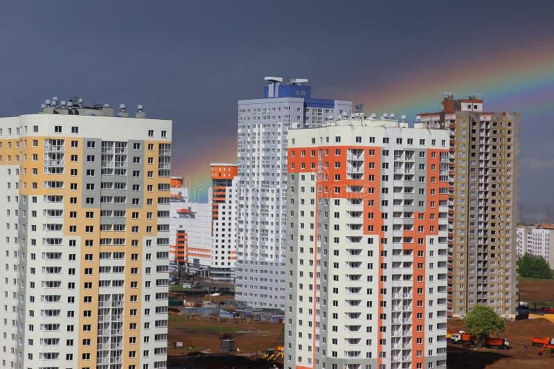 Casa de vários andares do bloco moderno novo no fundo escuro do céu em quatro cores: vermelho, alaranjado, cinza e branco Mau tem imagem de stock royalty free