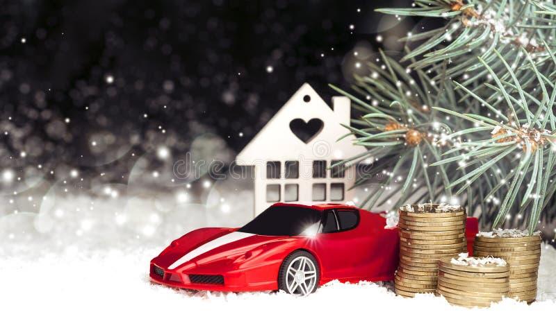Casa decorativa de madera en la nieve, coche, monedas foto de archivo
