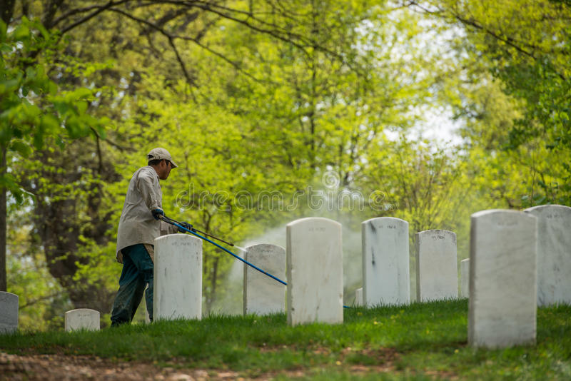 Casa del blanco de la C C , los E.E.U.U. - MAYO, 2 2014 - trabajador están limpiando las piedras sepulcrales en el cementerio de  fotografía de archivo libre de regalías