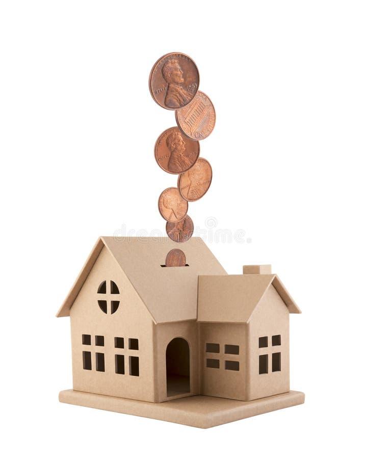 Casa del cartone con le monete che cadono nella scanalatura isolata su fondo bianco fotografia stock