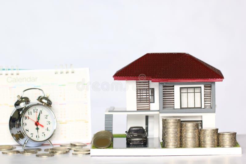 Casa del concepto del tiempo del impuesto, modelo y coche con el amontonamiento del dinero de las monedas foto de archivo libre de regalías
