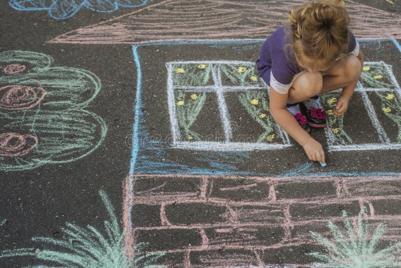 Casa del drenaje de la muchacha con tiza en el asfalto fotos de archivo libres de regalías