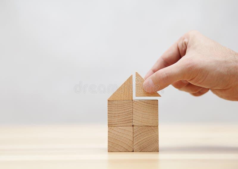 Casa del edificio de la mano con los bloques de madera fotos de archivo