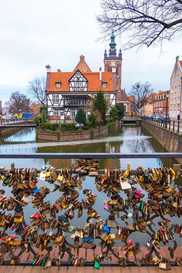 Casa del gremio de Miller y puente del amor en el canal en la ciudad vieja de Gdansk, Polonia fotos de archivo