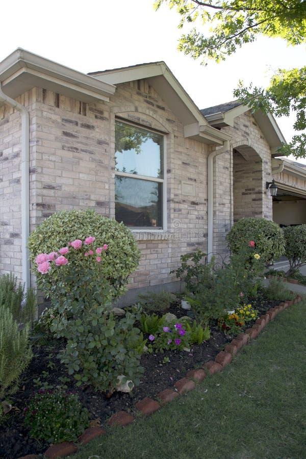 Casa del ladrillo con el jardín y el garaje imágenes de archivo libres de regalías