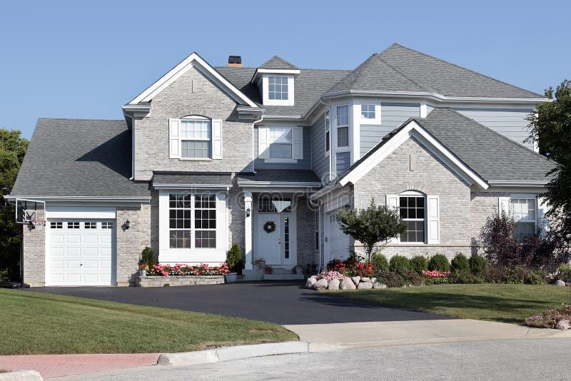 Casa del mattone con il raccordo blu fotografia stock