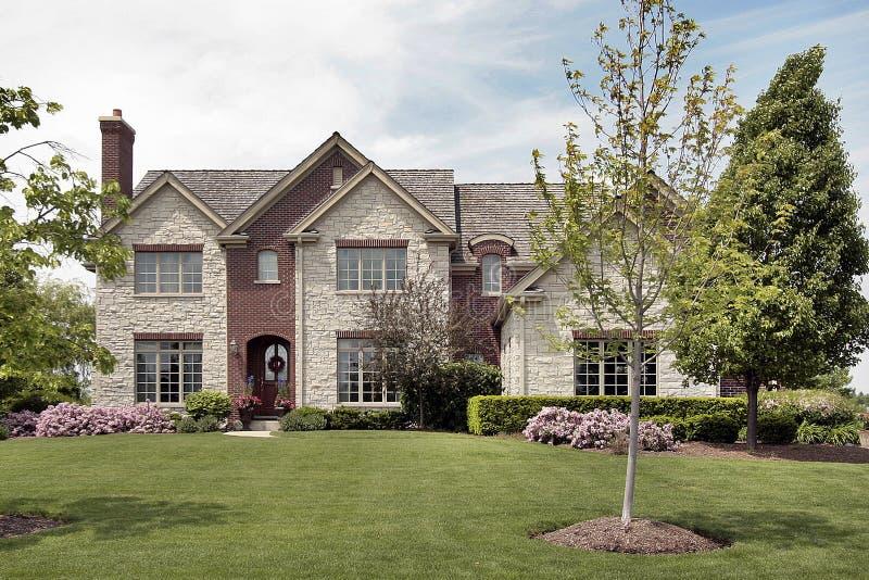 Casa del mattone e della pietra in primavera fotografia stock