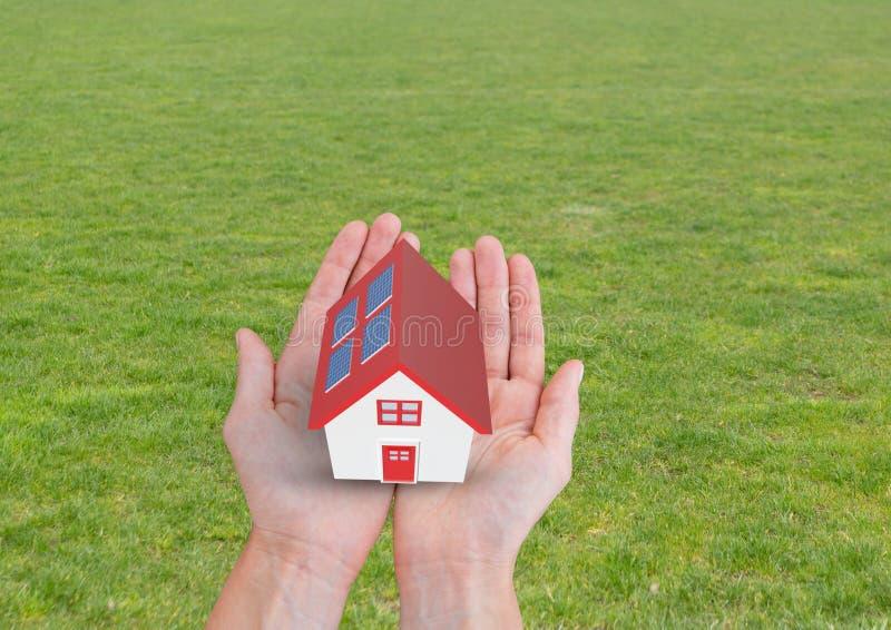 casa del panel solar con el tejado rojo en las manos ilustración del vector
