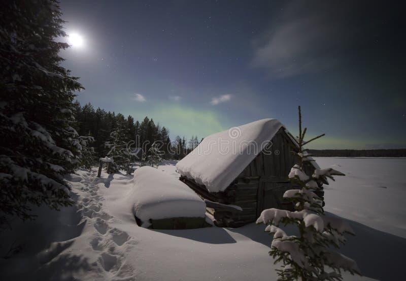 Casa del pueblo en las luces de la luna y del aurora borealis imagenes de archivo