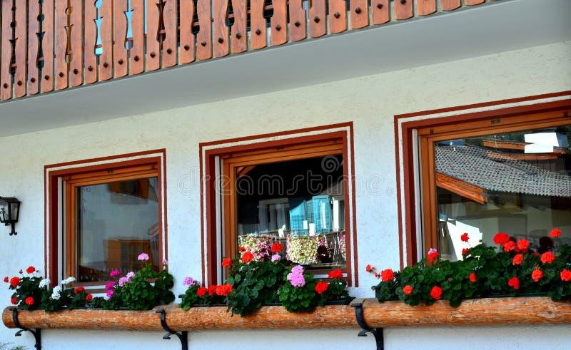 Casa del villaggio e tre finestre fotografia stock