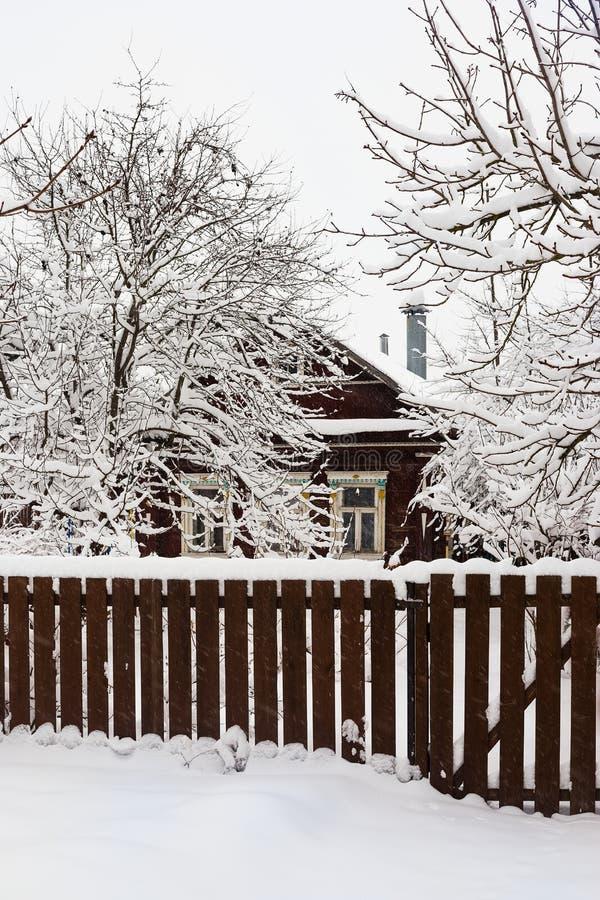 Casa del villaggio sotto neve dietro il recinto di legno immagini stock
