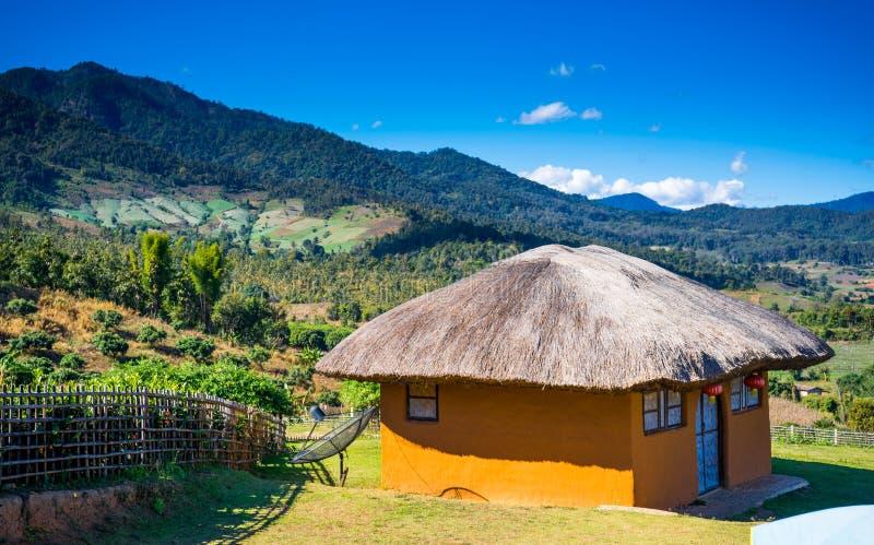 Casa dell'argilla con un tetto della paglia sui precedenti delle montagne nella città di Pai nel Nord della Tailandia Viaggio del fotografia stock libera da diritti