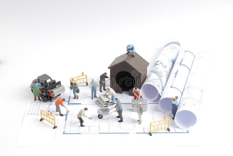 casa della costruzione sui modelli con la costruzione del lavoratore fotografia stock