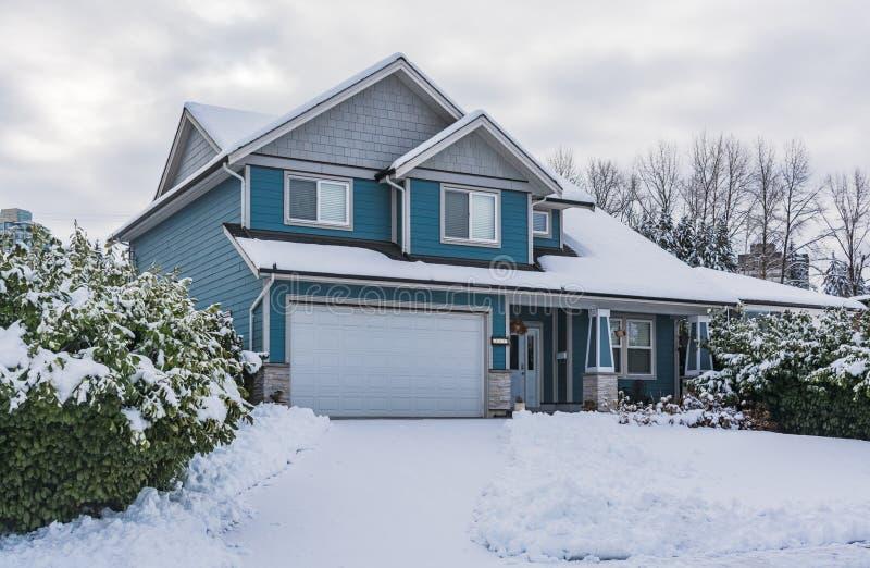 Casa della famiglia in neve il giorno nuvoloso di inverno immagini stock libere da diritti
