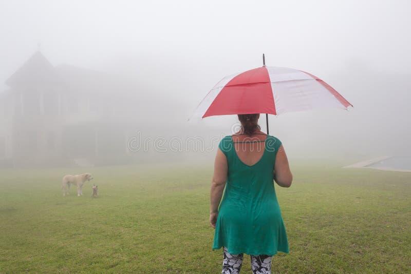 Casa della foschia dell'ombrello della donna immagine stock libera da diritti